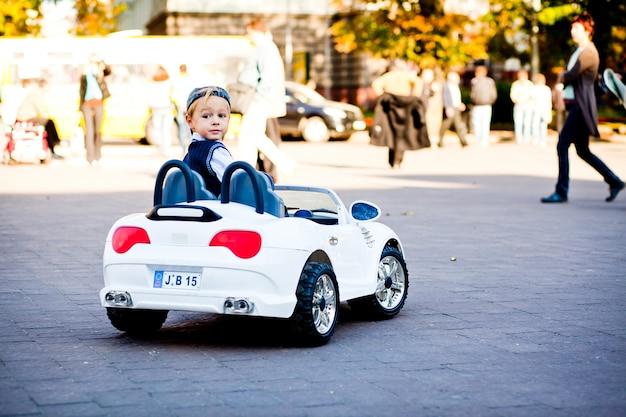 Ei, o que há? menino pequeno bonito conduz seu primeiro carro