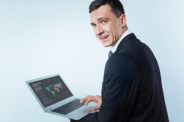 Ei, o que você está esperando. empreendedor de sucesso olhando para a câmera com confiança, segurando seu laptop e olhando para um mapa-múndi de transferências comerciais em segundo plano.