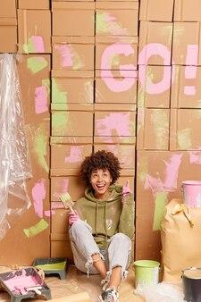 Ei, olha o que eu fiz! mulher alegre de pele escura e étnica aponta acima e mostra como pintou as paredes de um apartamento cercada por ferramentas de pintura, ocupada fazendo reparos em casa e redecoração de quartos