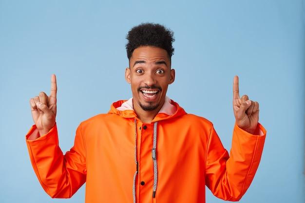 Ei, olhe para cima! feliz jovem atraente afro-americano usa capa de chuva laranja, sorri, fica de pé e quer chamar sua atenção para o espaço da cópia, aponta o dedo para cima.