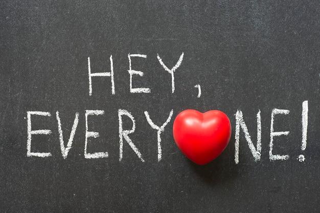 Ei, todos exclamação escrita à mão no quadro-negro com o símbolo do coração em vez de o