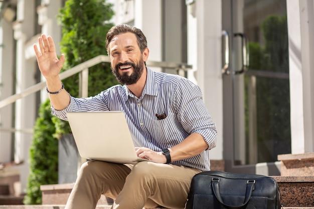 Ei você. homem adulto bonito e alegre cumprimentando seu vizinho enquanto usa o laptop ao ar livre