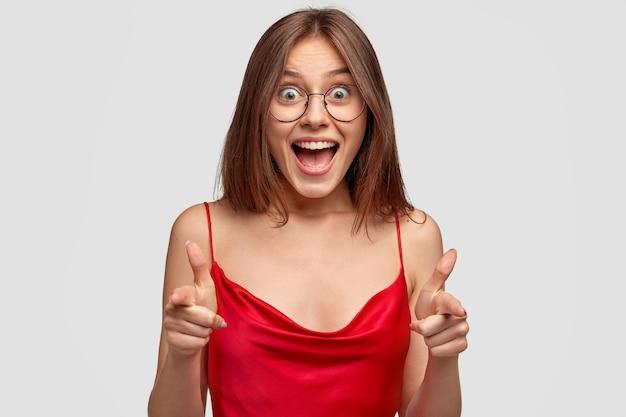 Ei você! linda e alegre modelo feminina tem expressão de alegria, sorri amplamente, faz gesto de arma com o dedo