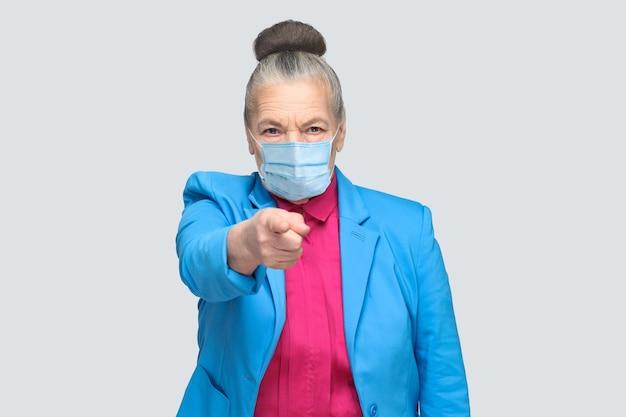 Ei você! mulher com máscara médica cirúrgica apontando para o dedo da câmera com cara séria. retrato de expressiva avó em pé com cabelo recolhido. foto de estúdio interno, isolada em fundo cinza