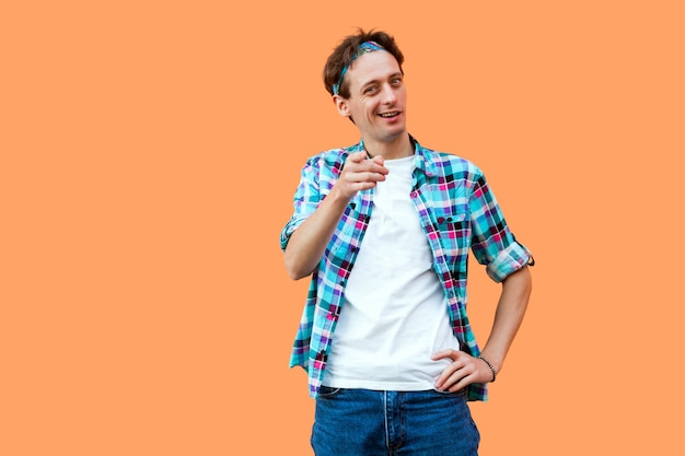 Ei você. retrato de jovem engraçado na camisa quadriculada azul casual e bandana em pé olhando e apontando para a câmera com um sorriso. tiro de estúdio interno, isolado em fundo laranja.