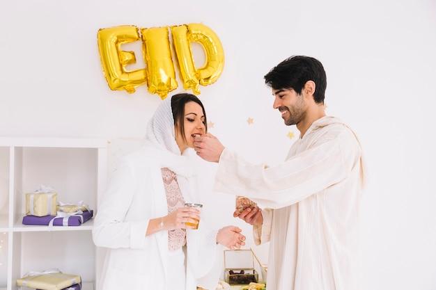 Eid al-fitr conceito com casal comendo biscoitos