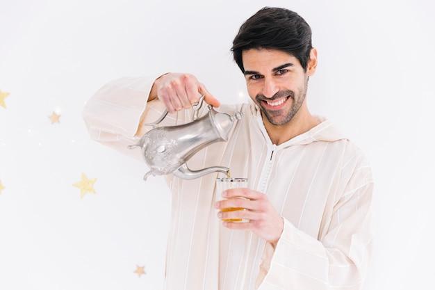 Eid al-fitr conceito com homem muçulmano derramando chá