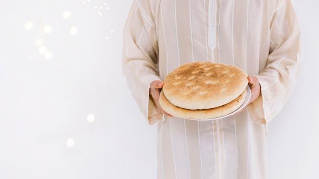 Eid al-fitr conceito com homem muçulmano segurando o pão
