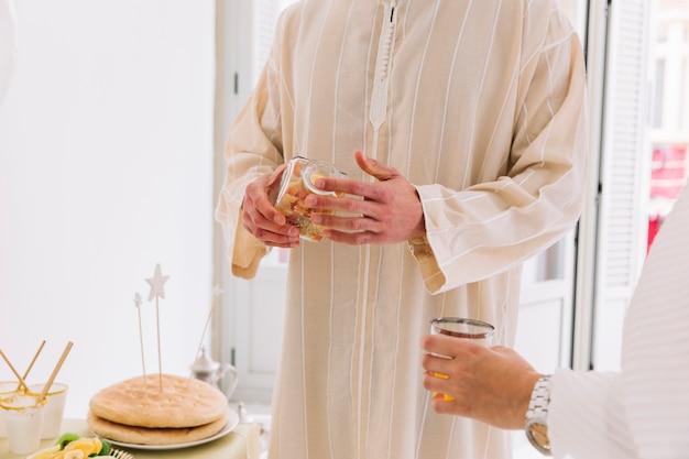 Eid al-fitr conceito com homem segurando jarra de cookies
