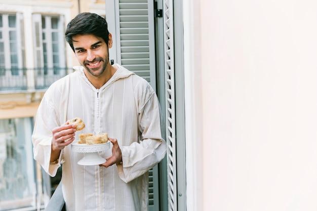 Eid al-fitr conceito com o homem muçulmano comendo
