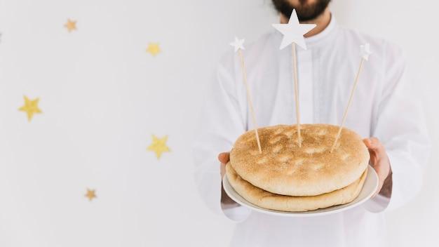 Eid al-fitr conceito com o homem segurando o prato de pão