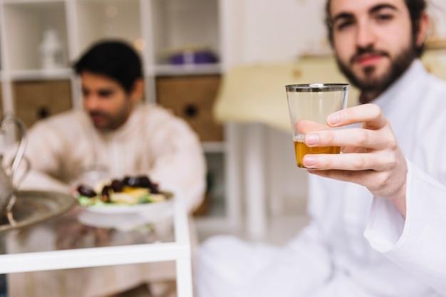 Eid conceito com homem mostrando o copo de chá