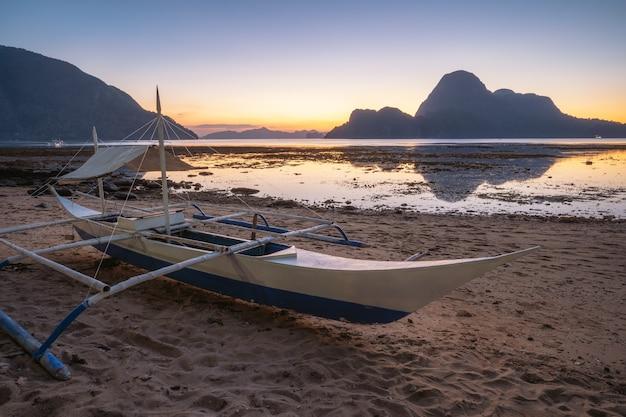 El nido, palawan, filipinas. barco de pesca tradicional na costa. ilha cadlao na luz do sol. temporada de férias.