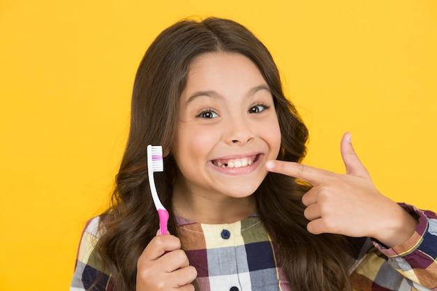Ela arrancou o dente de leite. criança feliz mostra dente de leite removido. menina pequena com a boca aberta e escova de dentes. a fada do dente irá visitá-la.