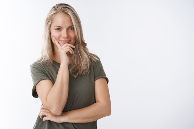 Ela conhece a chave para o sucesso. retrato de autoconfiante esportista feminina criativa fazendo plano, sorrindo, encantada e confiante, inclinando-se nos dedos, olhando ousando para a câmera sobre fundo branco