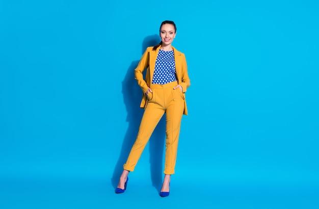 Ela é bonita, bem vestida, atraente, charmosa, elegante, alegre, companheira líder, segurando a mão no bolso isolado brilhante brilho vívido fundo de cor azul vibrante.