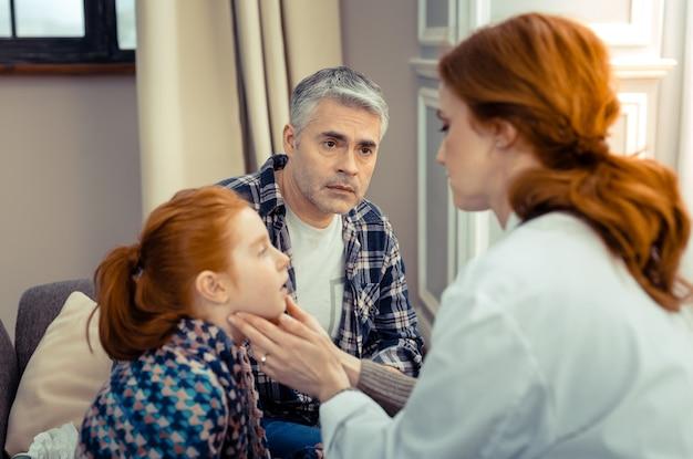 Ela esta bem. pai triste e preocupado olhando para o médico enquanto quer saber o estado de saúde de sua filha