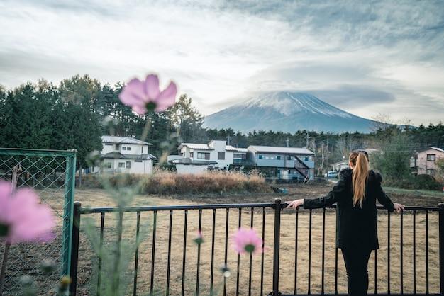 Ela está de pé e olha para o monte. fuji.