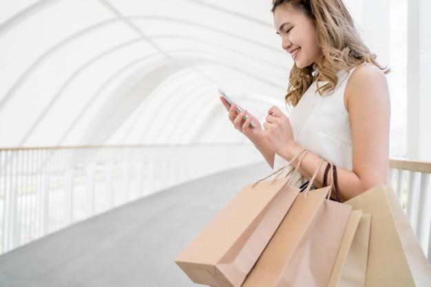Ela faz compras no shopping e usa um telefone celular para se comunicar com amigos e usa sacolas de papel para fazer compras.