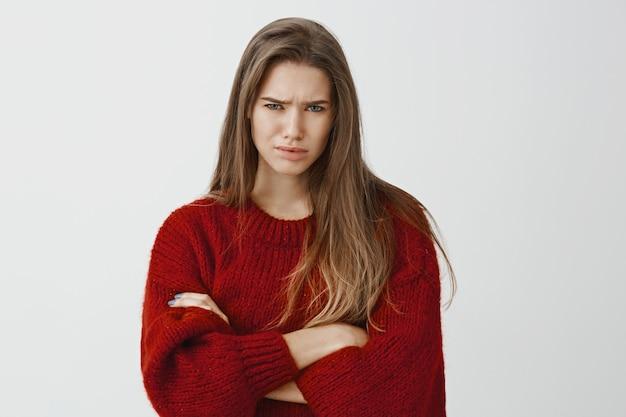 Ela não compra nessas linhas desajeitadas. aluna europeia descontente duvidosa na camisola solta vermelha, cruzando as mãos e franzindo a testa, expressando descrença e frustração sobre a parede cinza