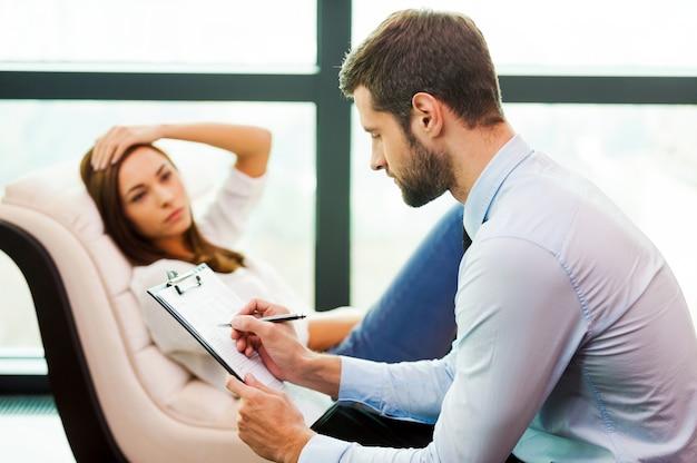 Ela precisa de um conselho especializado. jovem frustrada sentada na cadeira com a mão na cabeça, enquanto o jovem sentado perto dela e escrevendo algo em sua prancheta