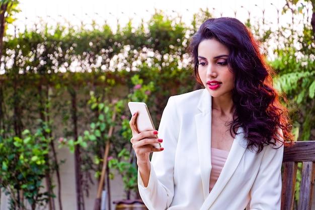 Ela usa celular no parque para pesquisar informações interne