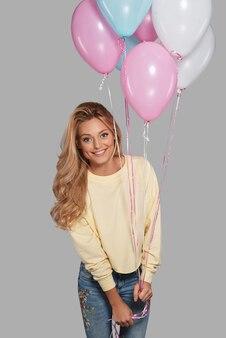 Ela vai trazer festa para você! mulher jovem e atraente sorridente segurando balões e olhando para a câmera em pé contra um fundo cinza