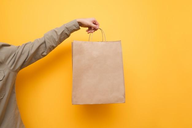 Elaborar uma sacola de compras na mão de um homem. substituindo o saco de plástico. conceito de pacote ecológico. copie o espaço
