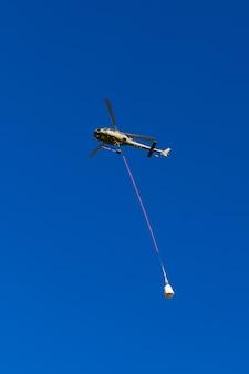 Elbrus, rússia - 16 de agosto de 2018: entrega de carga de aviação em altas montanhas usando um helicóptero.