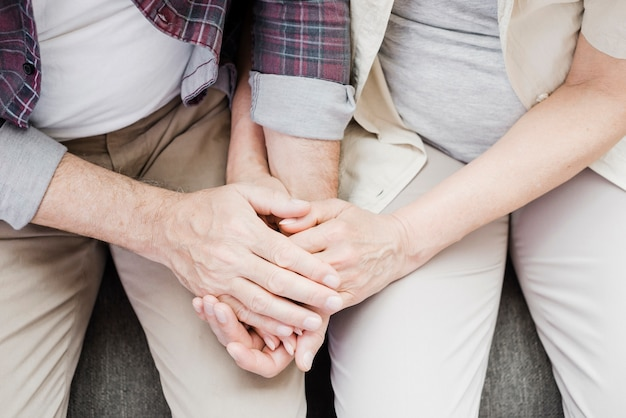 Elder casal segurando suas mãos