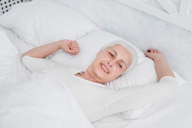 Elder mulher acordar na cama