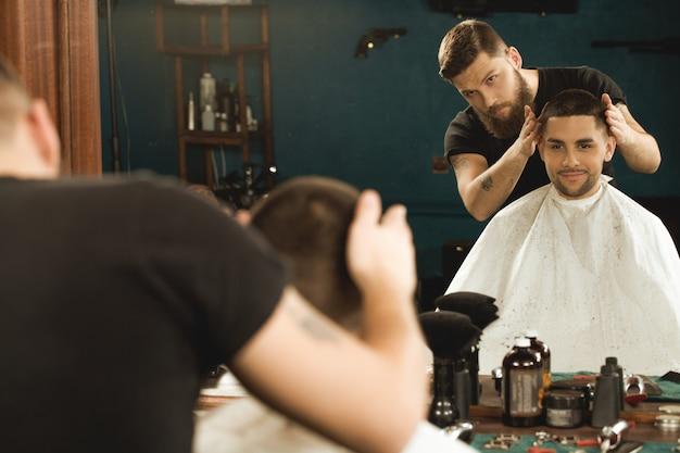 Ele ama o que vê. retrato de um cliente masculino sorridente feliz olhando para o espelho, sentado em uma cadeira de barbearia com um barbeiro, verificando seu corte de cabelo