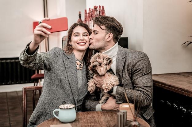 Ele, ela e seu cachorro. casal fazendo uma selfie romântica com o cachorro