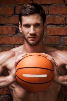 Ele está disposto a este jogo. jovem bonito e musculoso segurando uma bola de basquete