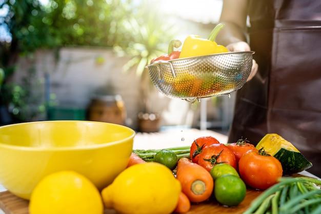 Ele está lavando frutas e legumes.