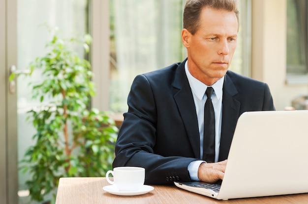 Ele está sempre em contato. homem maduro pensativo em trajes formais, trabalhando em um laptop enquanto está sentado à mesa ao ar livre