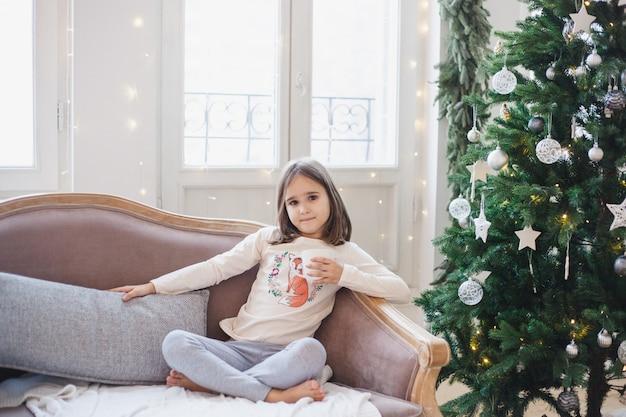 Ele está sentado no sofá esperando o feriado, o quarto está decorado para o natal
