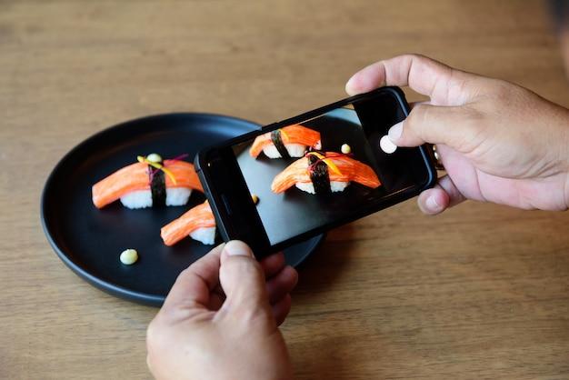 Ele está usando um celular, tirando uma foto de sushi, colocado em frente a um restaurante japonês.