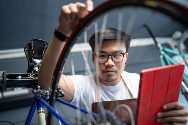 Ele está usando um tablet para verificar o produto. a entrada da loja de bicicletas cuida das bicicletas dos clientes para verificar a condição.