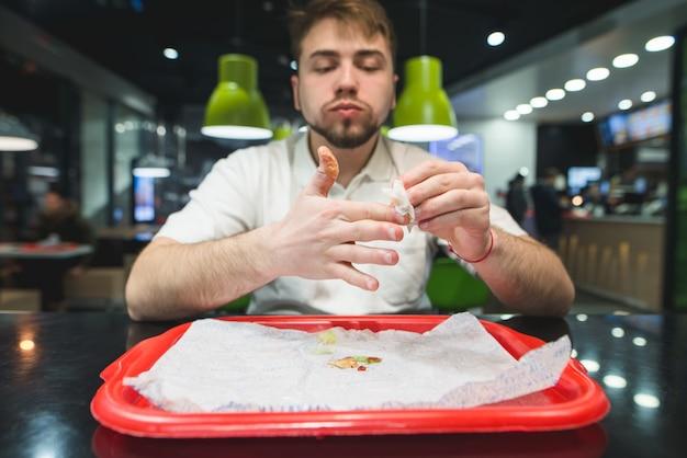 Ele limpa os dedos depois do almoço no restaurante de fast food. cara na mesa e bandeja limpa as mãos do molho