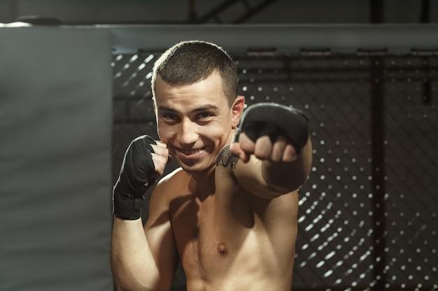Ele luta com um sorriso no rosto. jovem lutador profissional de mma sorrindo posando em uma jaula de luta