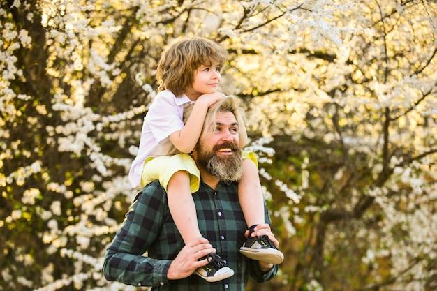 Ele o faz voar. pai e filho perto da flor da árvore sakura. feliz dia dos pais. celebrar o dia das crianças juntos. amor e valores familiares. relaxem ao ar livre juntos. nós somos família. criança abraça o pai dele.