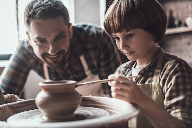 Ele tem mente criativa. garotinho desenhando em um vaso de cerâmica na aula de cerâmica, enquanto um homem de avental está perto dele e sorrindo