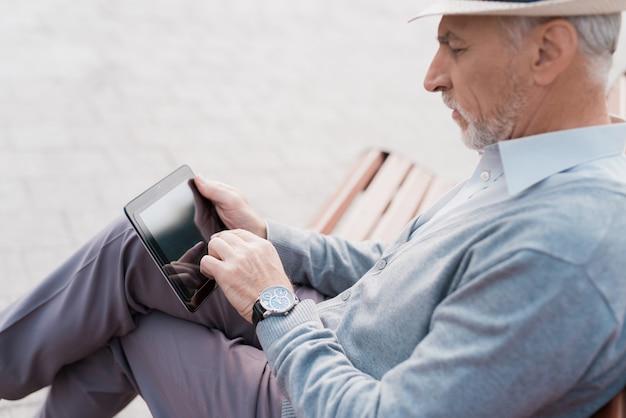 Ele tem um comprimido cinza nas mãos ele está lendo algo