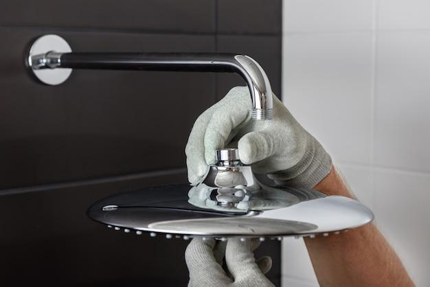 Ele trabalha as mãos instalam o tubo da torneira do chuveiro embutido