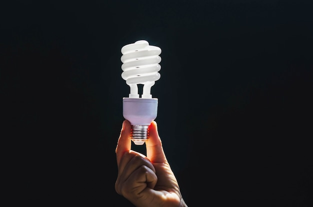 Electricidade e energia conceito - close-up da mão de uma mulher segurando uma lâmpada eficiente