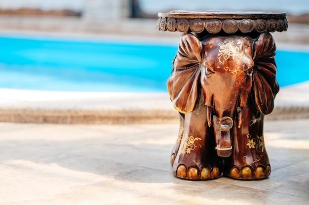 Elefante de madeira com gravura artística fica no chão perto da piscina, tradicional lembrança asiática. cadeira de elefante