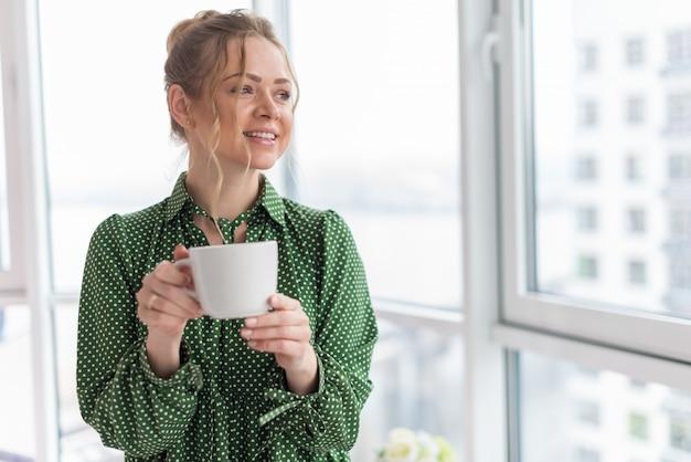 Elegância bela mulher loira em um arranha-céus istanding segurando uma xícara no contexto da janela