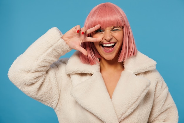 Elegante alegre jovem adorável com corte de cabelo curto rosa levantando a mão com o sinal de vitória no rosto, mantendo um olho fechado