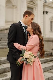 Elegante apenas alegre. casal de noivos. noiva e noivo andando perto do castelo velho. bouquet de noiva nupcial da flor